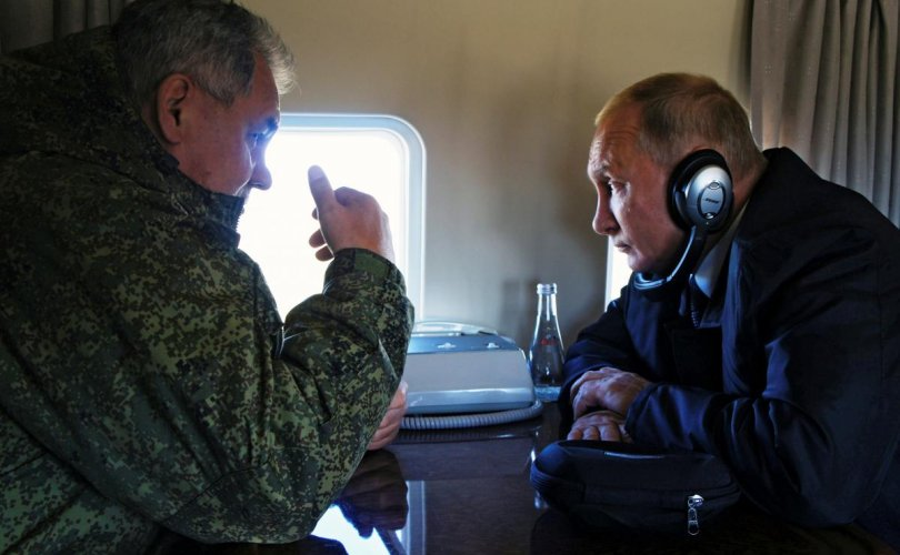 Russian President Vladimir Putin listens to Defence Minister Sergei Shoigu while flying over Tsugol training range in Zabaikalsky region
